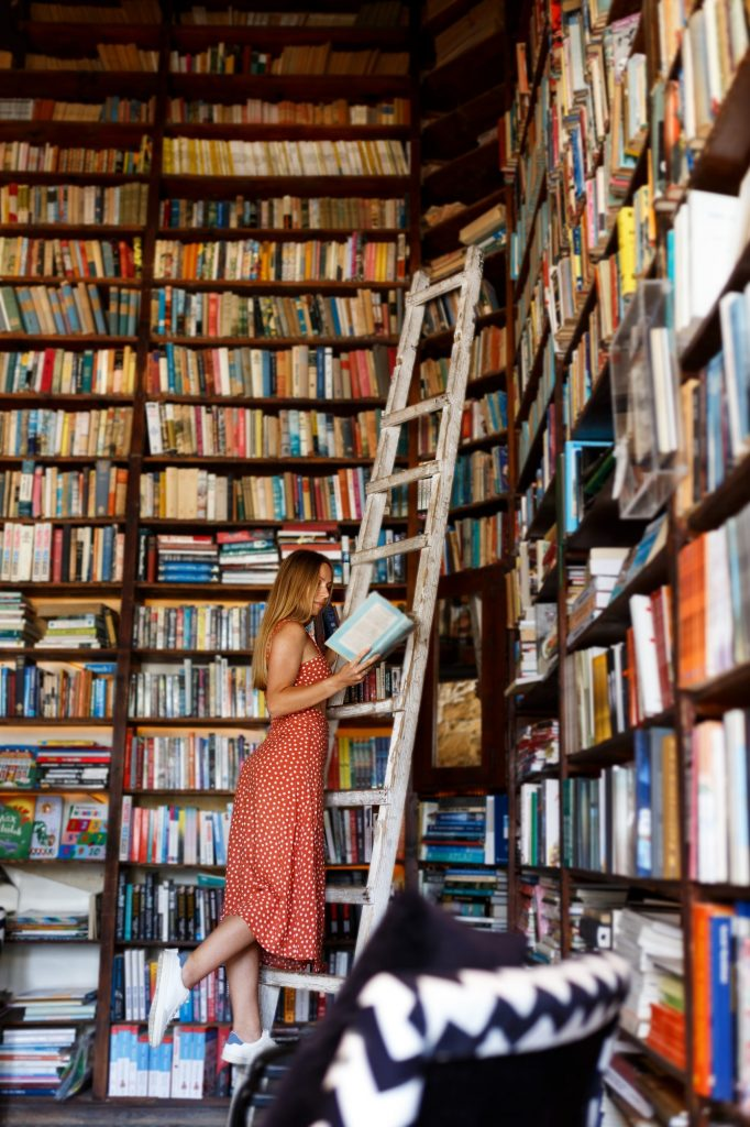 Girl reading book from bookshelves in bookstore,stands on wooden stairs