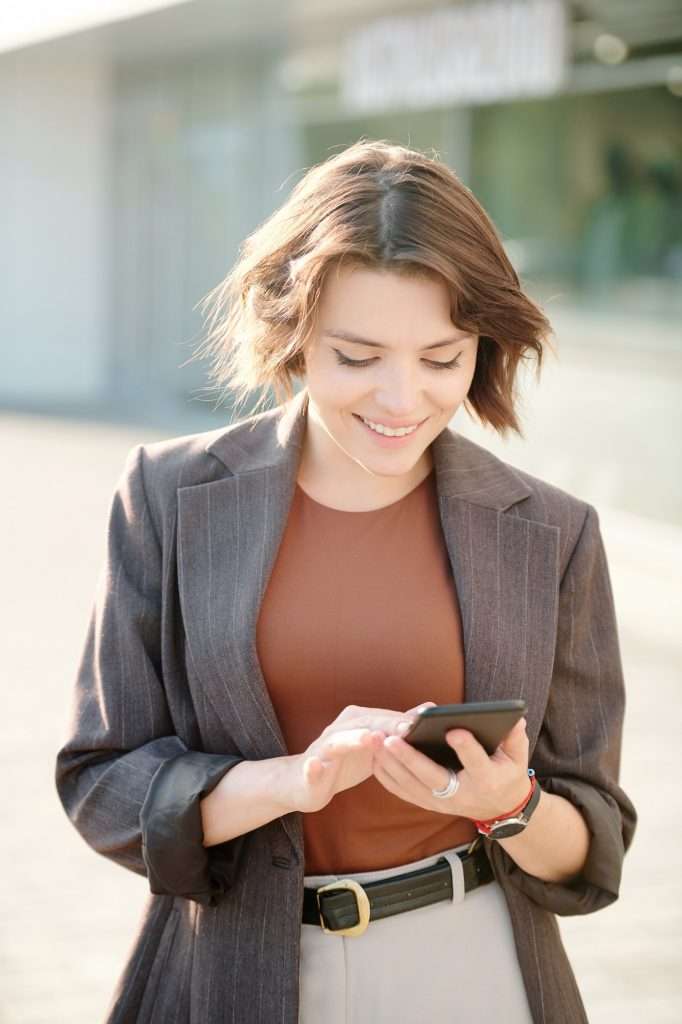 Happy and elegant young businesswoman scrolling through contacts in smartphone